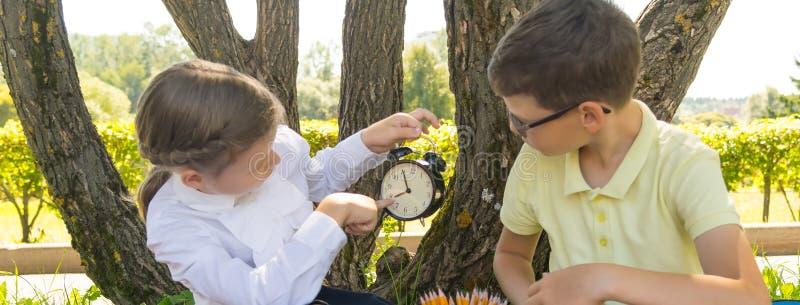 En parc, à l'air frais, la fille montre le temps de garçon sur l'horloge pour pour ne pas être en retard pour la leçon photos stock