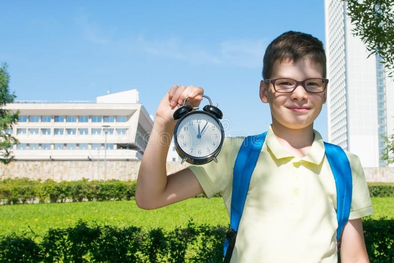 En parc, à l'air frais, le plan rapproché, l'étudiant tient un réveil dans ses mains et sourires que c'est midi photographie stock libre de droits