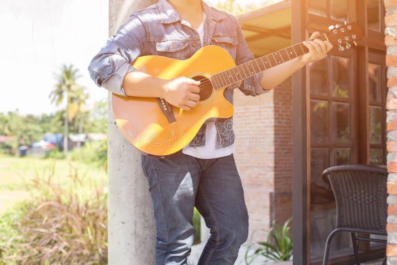 En parc, heureux pratiqu?s jeune la guitare de hippie par homme et ont plaisir ? jouer la guitare photo libre de droits