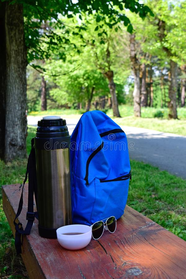 En parc sur le banc est un thermos et un sac à dos Le reste du touriste images stock