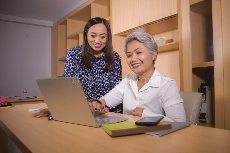 En partnersvrouwen die gelukkig en succesvol bij bureaulaptop computerbureau in baan vrouwelijke collega's samenwerken coworking stock afbeeldingen