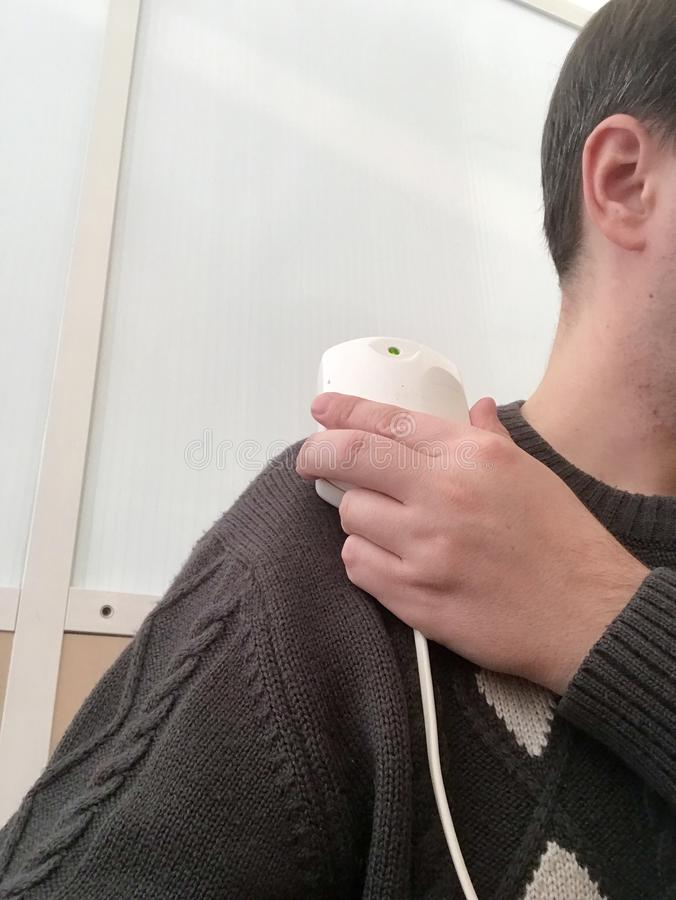 En patient i ett sjukgymnastikrum Magnetotherapy efter trauma Mannen rymmer apparaten som fäster det till hans skuldra royaltyfria bilder
