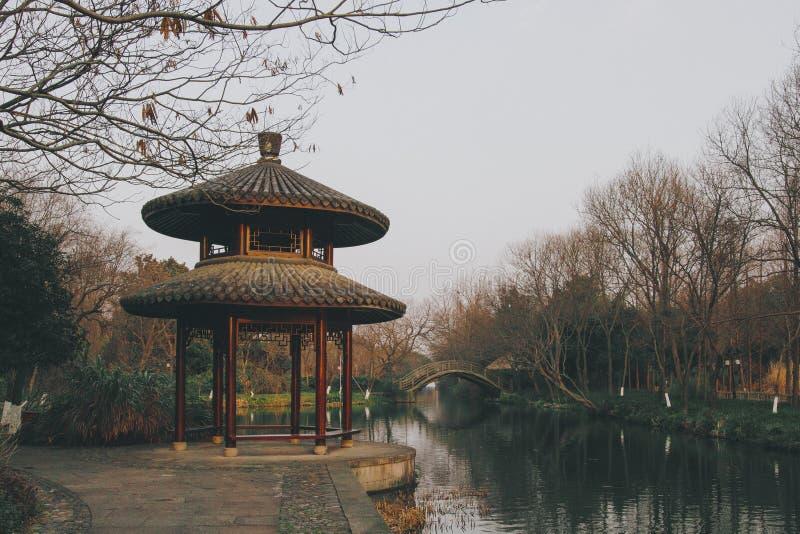 En paviljong för traditionell kines vid en flod i Hangzhou arkivfoton
