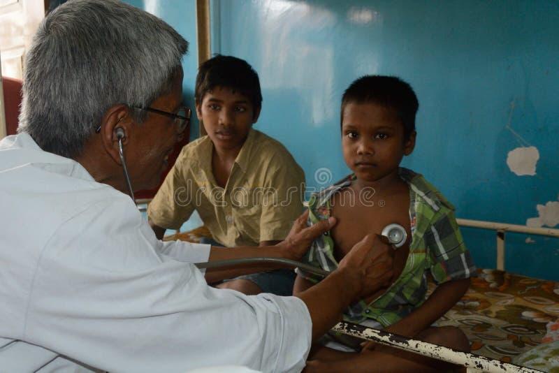 En pediatriker kontrollerar lite pojken med stetoskopet arkivfoto
