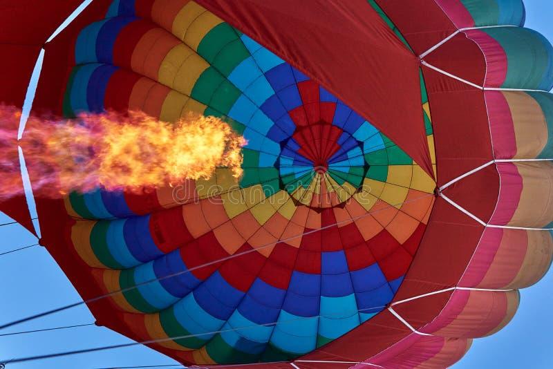 En pelare av flamman från en gasgasbrännare blåser upp en enorm mång--färgad ballong fotografering för bildbyråer