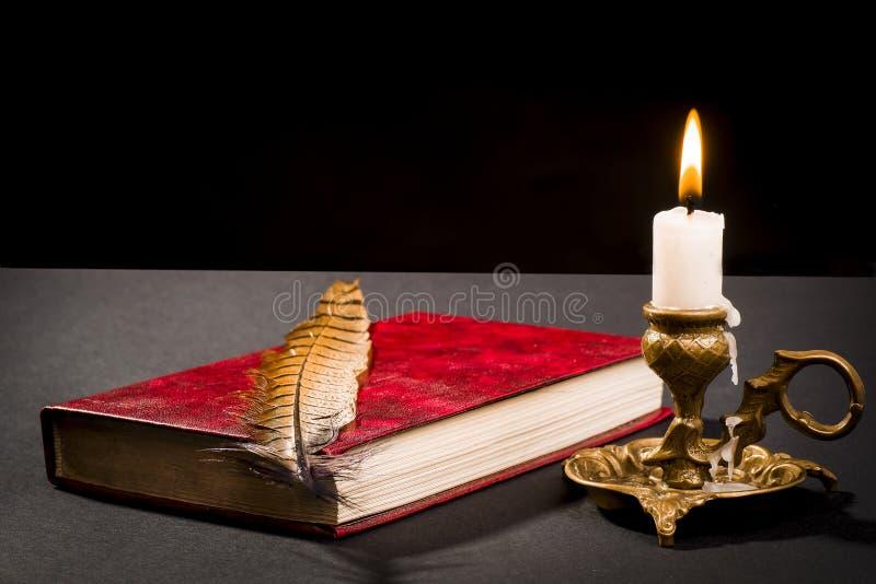 En penna på en bok och en tänd stearinljus i en ljusstake royaltyfria foton