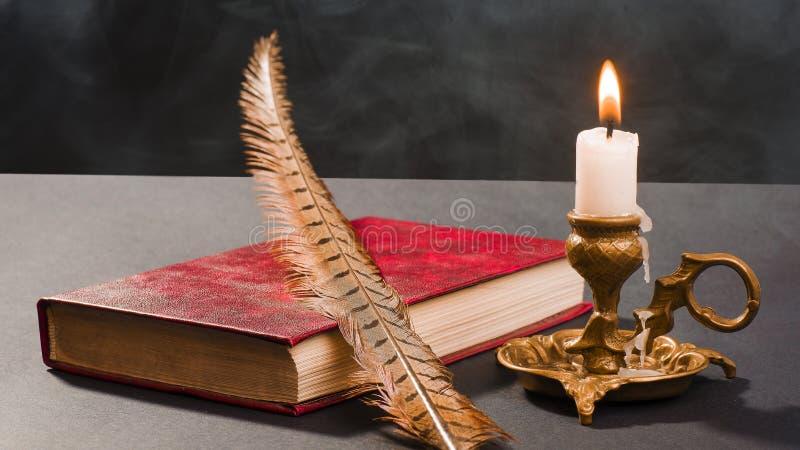 En penna på en bok och en tänd stearinljus i en ljusstake royaltyfri foto