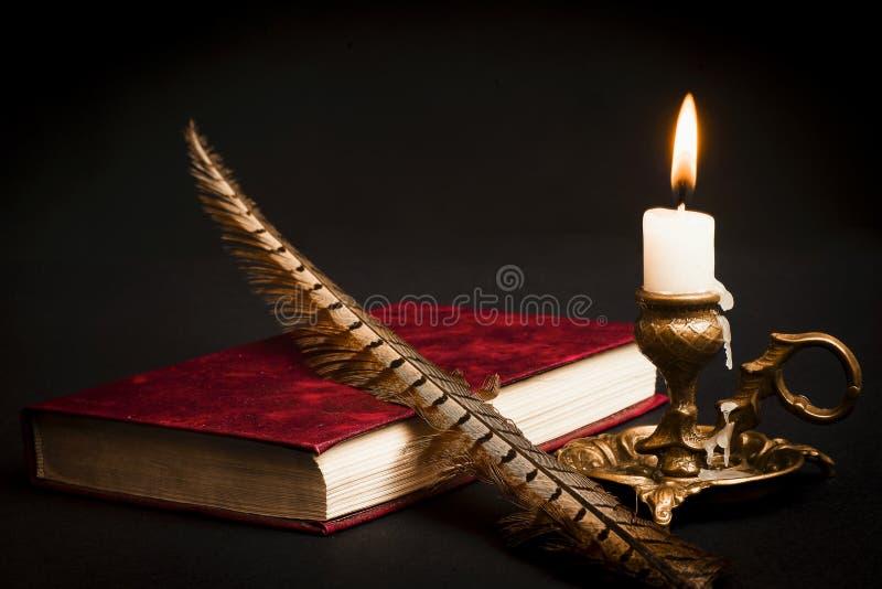 En penna på en bok och en tänd stearinljus i en ljusstake royaltyfri fotografi