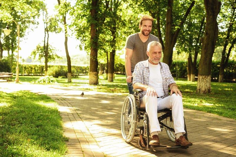 En pensionär på en rullstol och hans vuxna son går runt om parkera De är lyckliga och har gyckel arkivbild