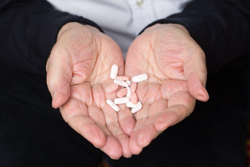 En pensionärs händer som rymmer medicinpreventivpilleren fotografering för bildbyråer