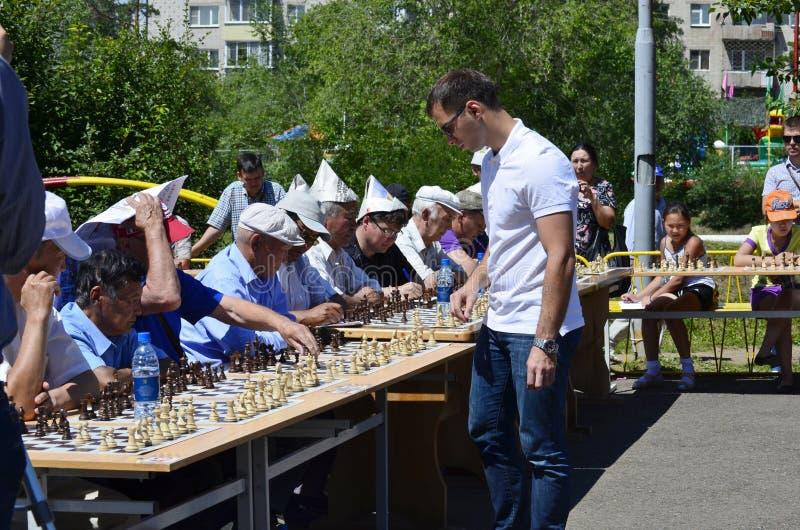 En period av en samtidig lek av en grandmaster med enkla schackspelare arkivfoton