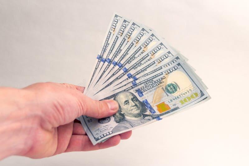 En person ger eller tar amerikanska tusen dollar Fan av hundra dollarräkningar i vänstersidahanden av en man Muta eller lön corr royaltyfri foto