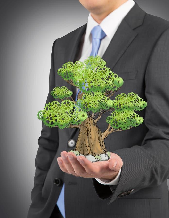 En person i formell dräkt rymmer ett skissat träd på gömma i handflatan royaltyfri foto