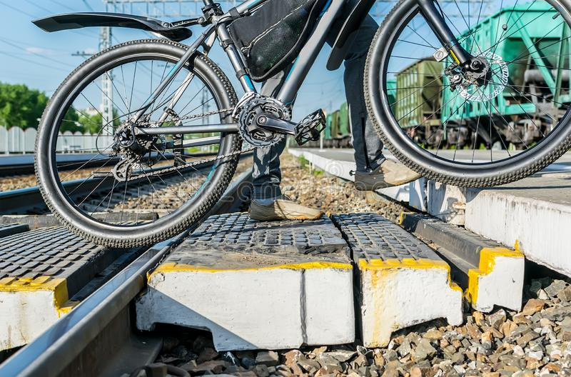 En person korsar en övergångsställe med en cykel på stängerna av järnvägsstationen royaltyfri fotografi