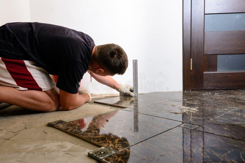 En person med en laser-nivå kontrollerar den installerade golvtegelplattan arkivfoton