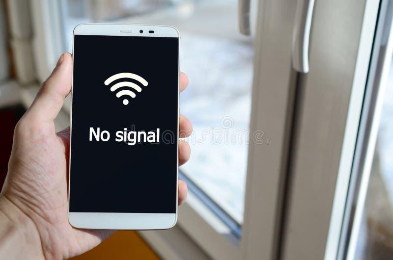 En person ser en vit inskrift på en svart smartphoneskärm arkivfoton