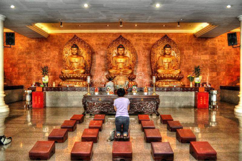 En person som ber i en Bhuddha tempel arkivfoto
