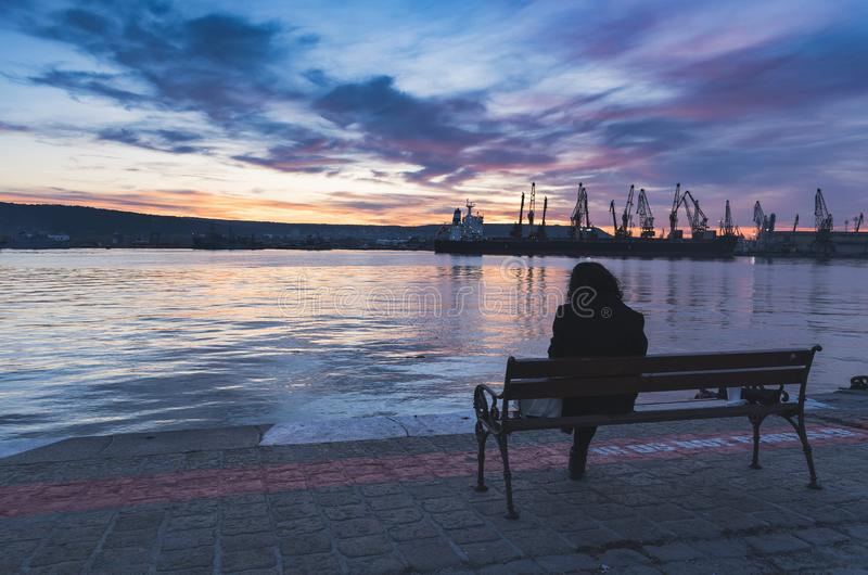 En person som håller ögonen på solnedgången över havsstationen i Varna royaltyfri foto