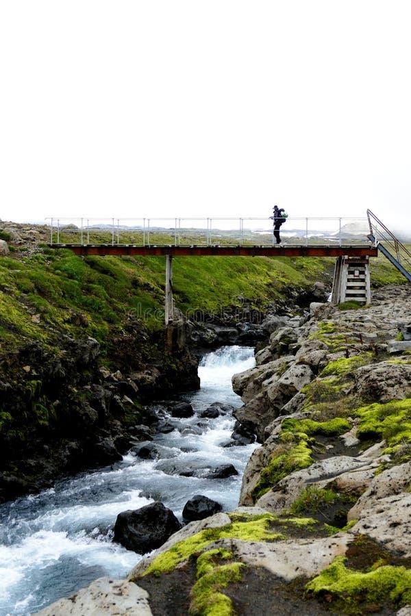 En person som i början korsar träbron av etapp två av det Fimmvörduhals bergpasserandet, Island royaltyfri foto