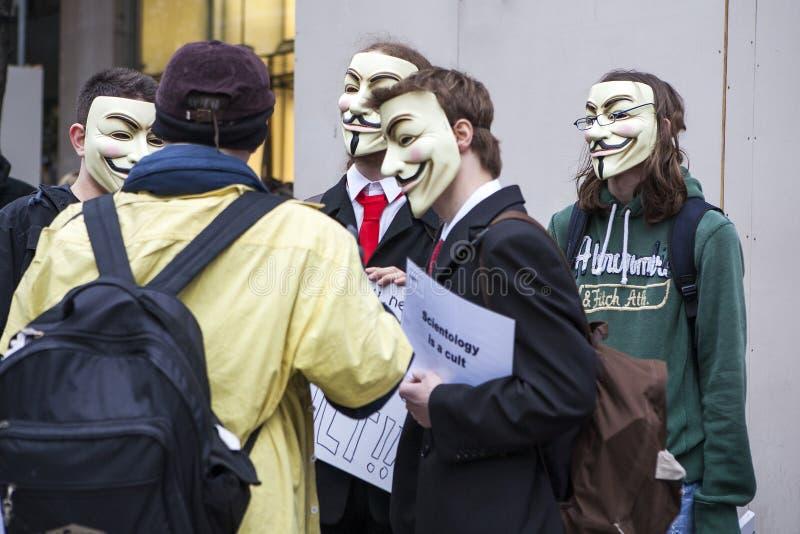 En person som protesterar som bär en Guy Fawkes maskering, rymmer ett plakat arkivfoton