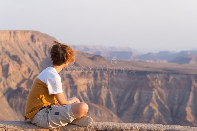 En person som ser fiskflodkanjonen, scenisk loppdestination i sydliga Namibia Expansiv sikt på solnedgången Reslust t royaltyfri bild