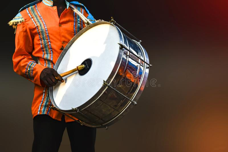 En person som spelar trumskinnet, - trumskinnet är ett musikinstrument som låtas, av att slås eller skrapning av en drevkarl arkivbild