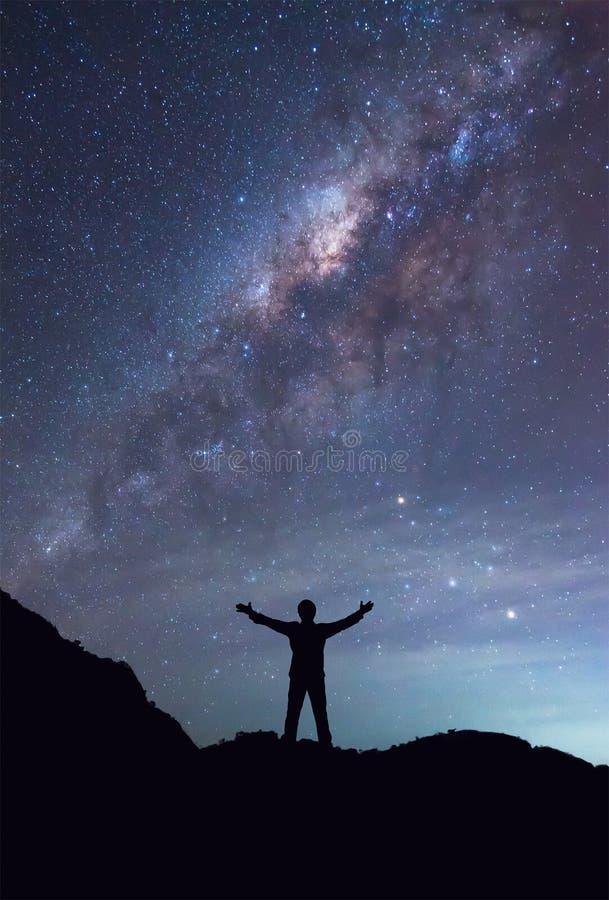 En person står bredvid handen för Vintergatangalaxspridning på arkivbilder