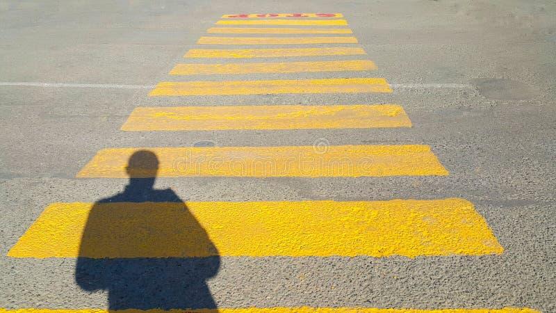 En person står i början av en övergångsställe, var det är det skriftliga stoppet och väntar på passagetiden, på gulingen arkivfoto