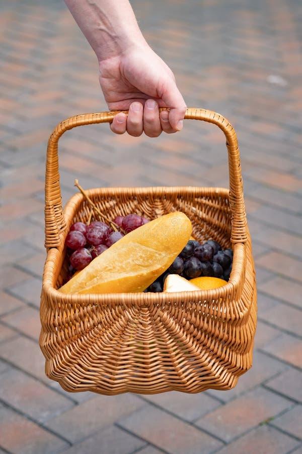 En picknickkorg med ingredienserna för en lunch i den öppna luften En man rymmer en picknickkorg royaltyfria bilder