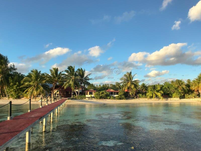 En pier leder från ett gazebo över vattnet till stranden med en sandstrand inlagd med bungalows.kopieringsutrymme arkivbilder