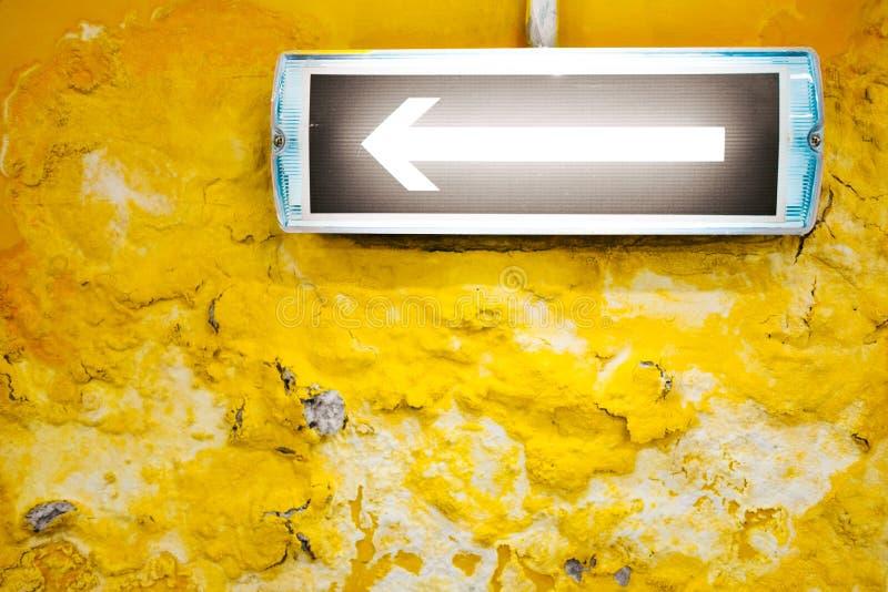 En pil på den gula väggen arkivfoton
