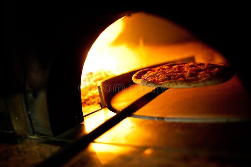 En pizza i en ugnsbränning royaltyfri fotografi