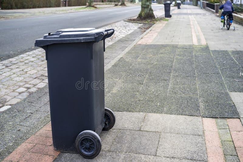 En plast- dumpster står på sidan av vägen som väntar på en avskrädelastbil i bygden, i bakgrunden ritter för ett barn royaltyfri foto