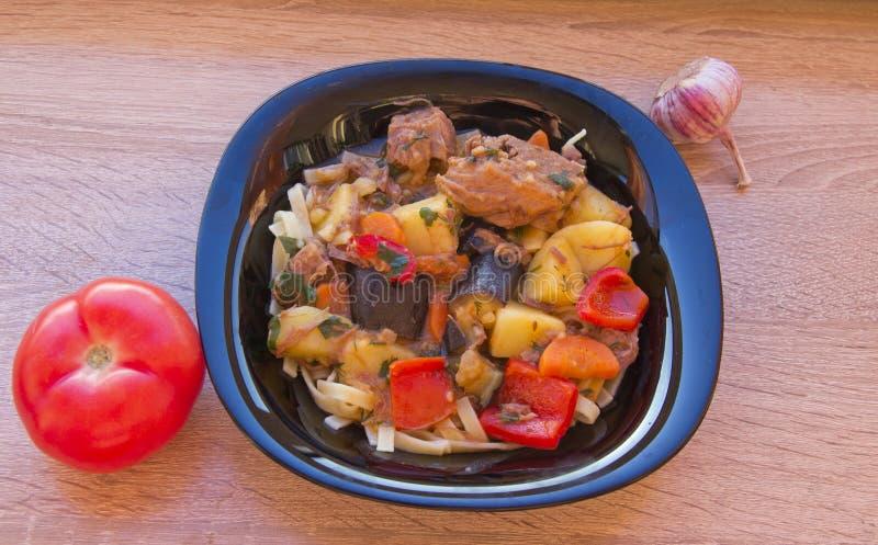En platta av den lagade mat maträttlagmanen på en trätabell royaltyfri foto