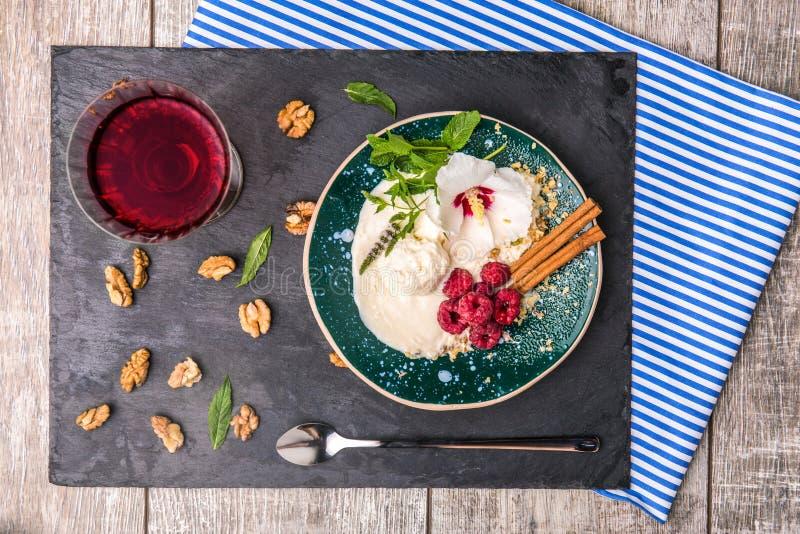 En platta av vaniljglass med blomman, bär och kryddor Ett kallt mellanmål och ett exponeringsglas av fruktsaft på en träbakgrund royaltyfria bilder