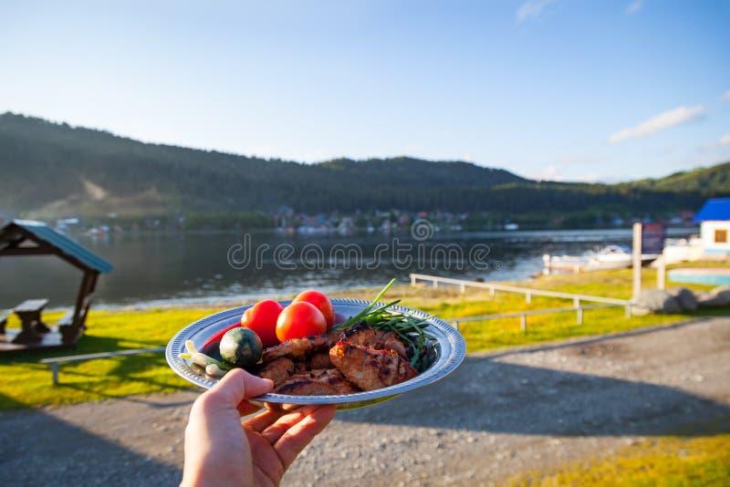 En platta med grillat läckert kebabkött med nya grönsaker, tomater och gurkor på en utsträckt arm mot fotografering för bildbyråer