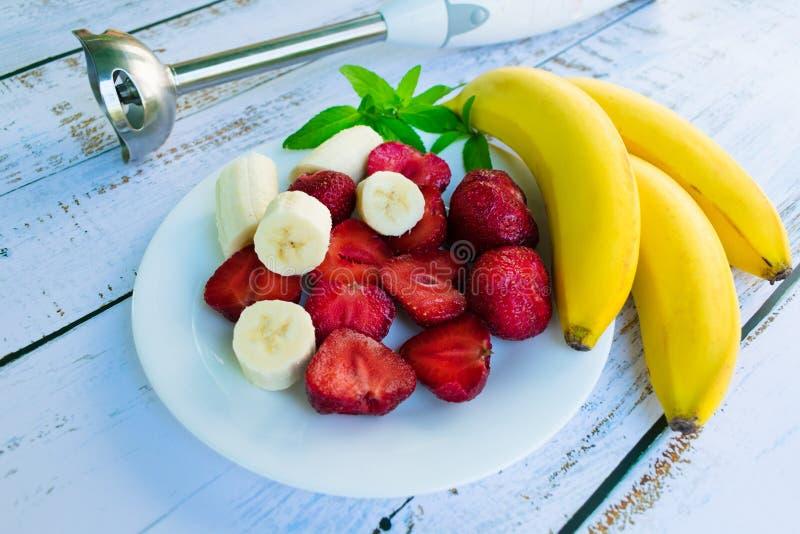 En platta med jordgubbar och en banan och en blandare på en vit trätabell fotografering för bildbyråer