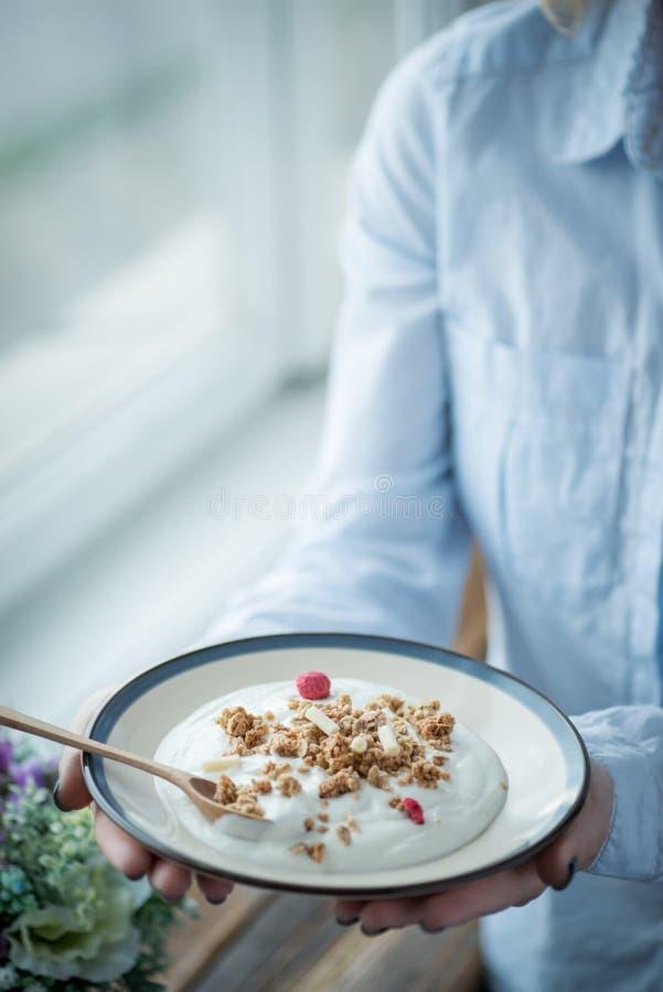 En platta med ny yoghurt i kvinnas händer royaltyfri bild