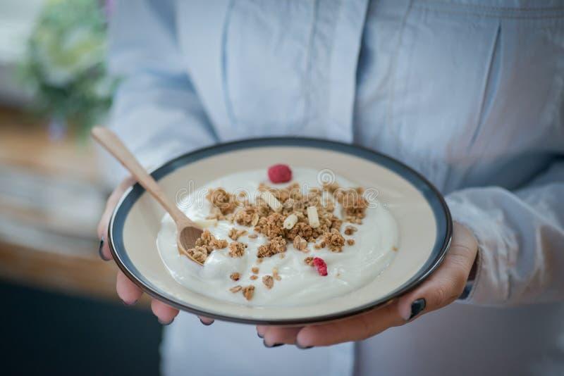 En platta med ny yoghurt i kvinnas händer arkivbilder