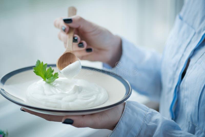 En platta med ny yoghurt i kvinnas händer royaltyfria bilder