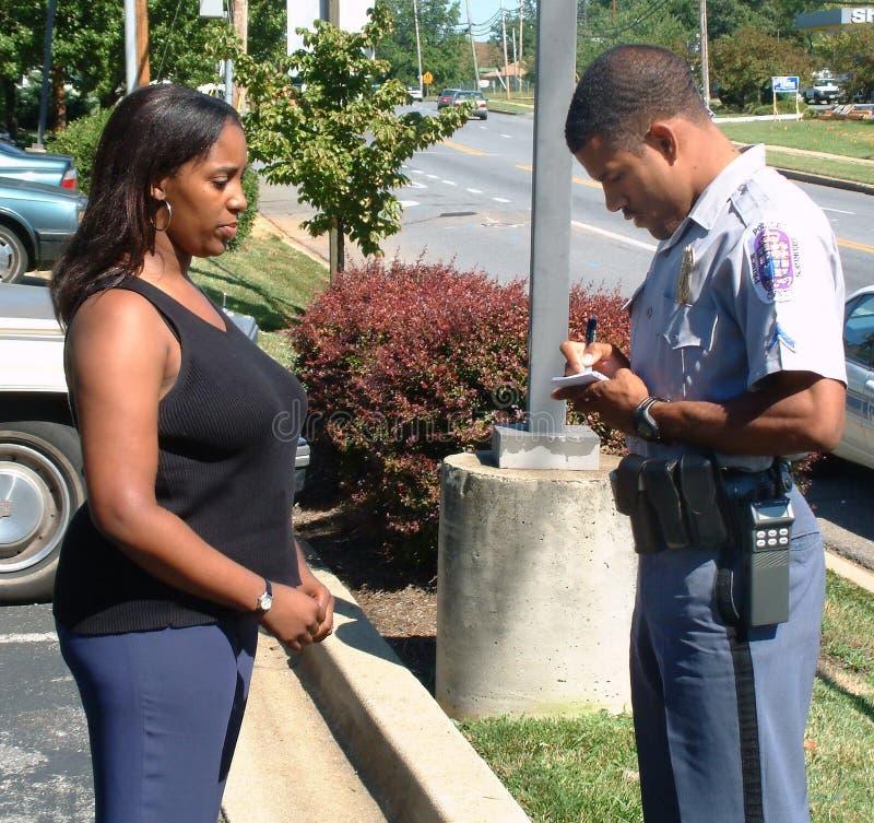 En po; istjänstemannen tar en rapport av ett brott från en kvinna arkivbilder