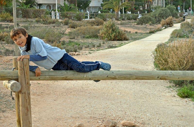 En pojke överst av en träport royaltyfri bild