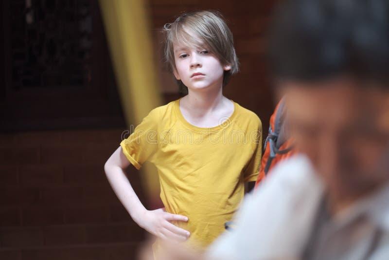 En pojke av skolaåldern med en stilfull frisyr royaltyfri fotografi