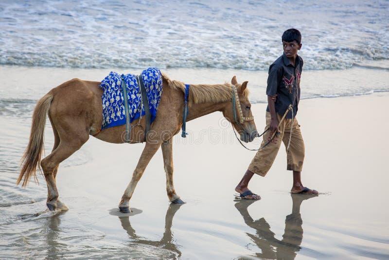 En pojke för hästridning som söker hennes klienter på den Patenga stranden, Chittagong, Bangladesh arkivbilder