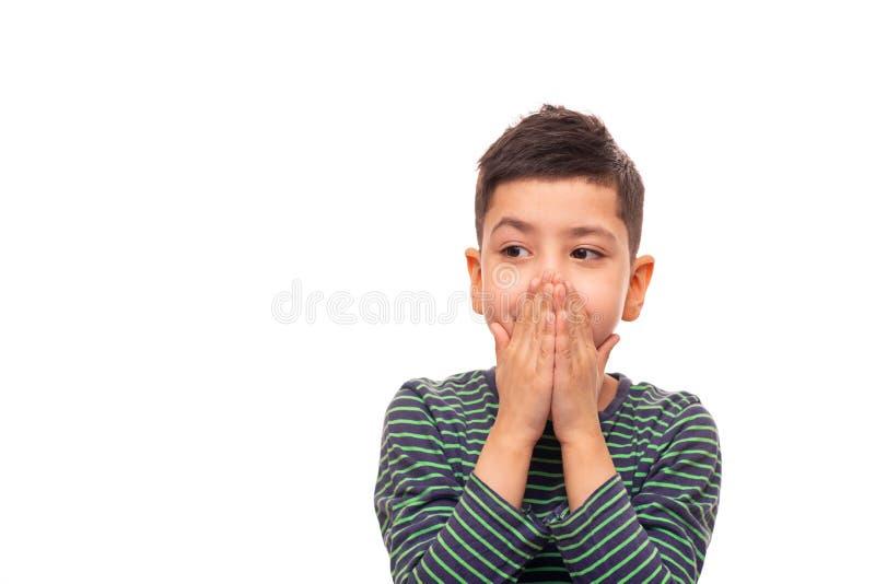 En pojke generas om något och med hans gömma i handflatan dolde hans mun som hindrar hans sinnesrörelser royaltyfria bilder
