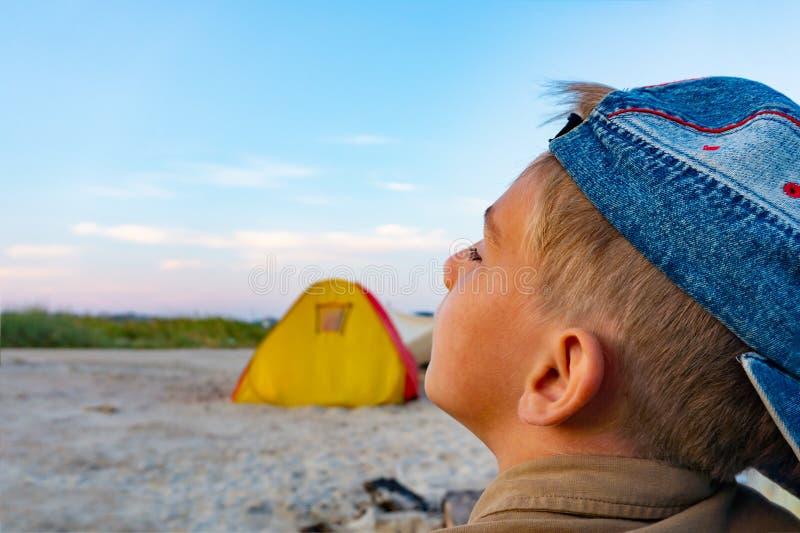 En pojke i en blå baseballmössa på aftonsolnedgången ser upp mot ett gult tält royaltyfri foto