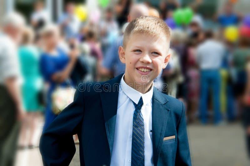 En pojke i en dräkt står nära hans skola på bakgrunden av peop royaltyfria foton