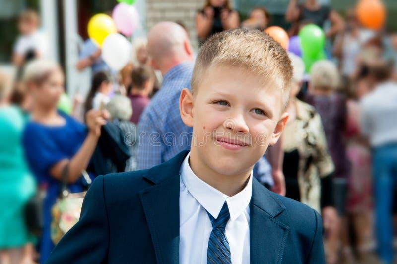 En pojke i en dräkt står nära hans skola på bakgrunden av peop royaltyfri fotografi