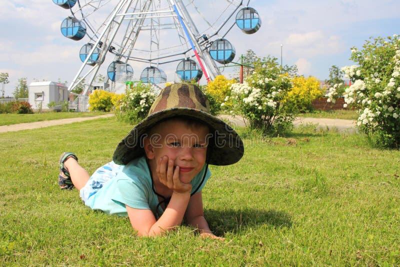 En pojke i en hatt som ligger på gräset i, parkerar royaltyfria foton