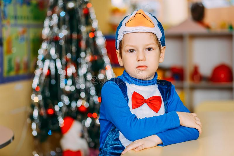 En pojke i karnevaldräkt i dagiset, pingvindräkt arkivfoton